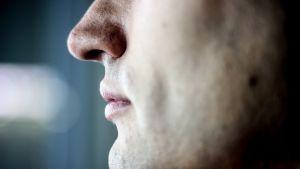 Miehen kasvot rajattuna nenästä alaspäin.