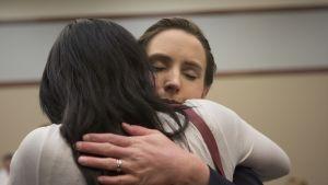 Kaksi nuorta naista halaa toisiaan.