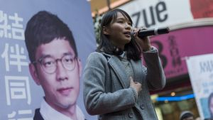 Harmaaseen päällystakkiin pukeutunut Agnes Chow puhuu mikrofoniin vaalijulisteen edessä.