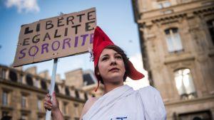 """Ranskan kansallissymboliksi Marianneksi pukeutunut mielenosoittaja kantaa julistetta, jossa luki """"Vapaus, sisaruus, tasa-arvo""""."""