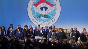 Kuvassa joukko pukumiehiä seisoo lavalla ja kuuntelee keskellään olevaa YK:n Syyria-lähettilästä.