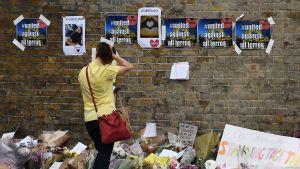 Nainen katsoo kukkia Finsbury Parkin terrori-iskupaikalla.