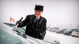Erkki Kukkonen putsaa autonsa tuulilasia toiseksi viimeisenä työpäivänään Järvenpään kaupunginjohtajana.