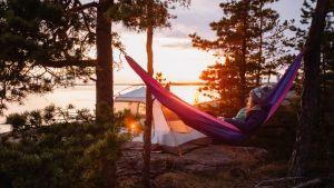 Nainen makoilee riippumatossa ilta-auringossa.
