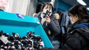 Naiset tutkivat maskotteja kisakaupassa.
