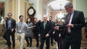 Senaatin republikaanijohtaja Mitch McConnell toimittajien ympäröimänä budjettisovun jälkeen.