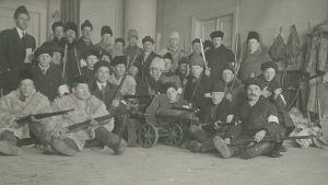 Sotainen ryhmä Tornion taistelun jälkeen. Tornion taistelussa saatua sotasaalista valtaajineen Tornion VPK:n talolla vuonna 1918.