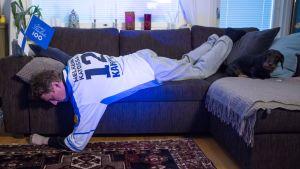 Mies nukkuu huonossa asennossa sohvalla.