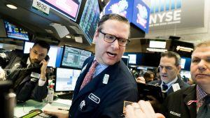 New Yorkin pörssi toiminnassa 9. helmikuuta 2018. Keskellä mies kommentoi jotain taaksepäin, ympärillä on muita miehiä, yksi on puhelimessa, toinen näppäilee tablettitietokonetta, kolmas katselee ilmeisesti monitoreita.