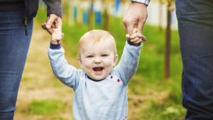 Lapsi kävelee pidellen äitiä ja isää käsistä.