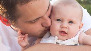 Isä pussaa lastaan poskelle.