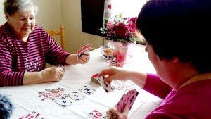 Aili Vuorio ja Sirpa Jaara pelaavat korttia.