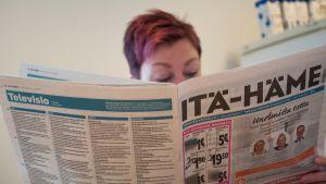 Nainen lukee sanomalehteä