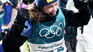 Hanna Öberg juhlii olympiakultaa Korean olympialaisten ampumahiihdon normaalimatkan jälkeen.