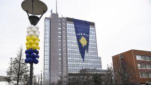 Isoa Kosovon lippua ripustetaan juhlistamaan maan kansallispäivää. Pylväissä on ilmapalloja.