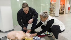 Vesa Holmström ensiapukoulutuksessa asentaa defibrillaattoria käyttöön. Kouluttajana Sari Anttila.