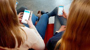 Kaksi tyttöä viestittelee puhelimella.