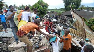 Ihmisiä pelastamassa omaisuuttaan maanvyöryn jälkeen.