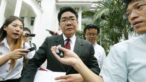Japanilaismiehen asianajaja Kong Suriyamonthon (kesk.) lehdistön ympäröimänä Bangkokin poliisiaseman edustalla skandaalin ollessa valloillaan syyskuussa 2014.