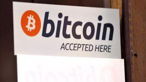 Virtuaalivaluutta Bitcoinin logo liiketilan ikkunassa Helsingissä.