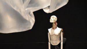 Nuken valaistut kasvot suunnattuna ilmassa heiluvaan muoviin, Croak nukketeatteriooppera.