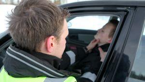 Auttaja kokeilee liikenneonnettomuuden uhrin pulssia.