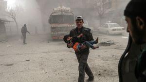 Mies kantaa haavoittunutta lasta.