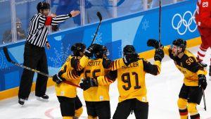 Tuomari näyttää maalia olympiafinaalissa, Saksa juhlii kuvan etualalla