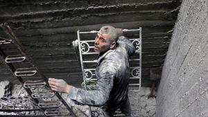 Verta vuotava mies etsii pommituksista selvinneitä Doumassa.