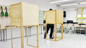 Äänestäjä äänestyskopissa Iivisniemen koululla Espoossa.