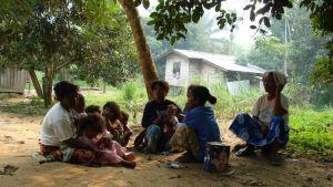 Joukko naisia ja lapsia hiekalla puun alla, pieniä puutaloja ja sademetsää.