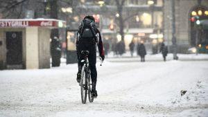 Pyöräilijä Helsingin keskustassa pöpperöisessä talvikelissä.