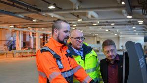 Pinomaticin projektipäällikkö Tuomo Kauppila sekä CLT Plantin Petri Hyvönen ja Aki Virtaniemi tutkimassa tehtaan suunnitelmia.