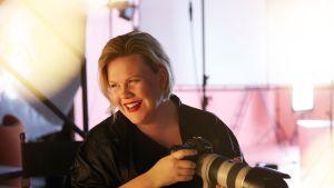 Kuvassa nainen kameran kanssa.