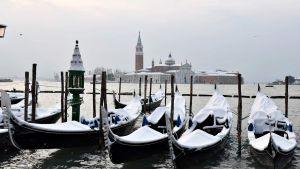 San markon aukion rannalla lumipeitteisiä gondoleita Venetsiassa.