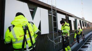 Metallityöväenliiton kylttiä irroitetaan Hakaniementie 1:n katolla