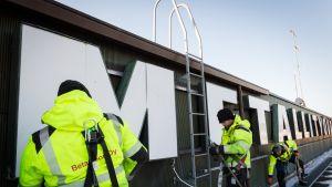 Metallityöväenliiton kylttiä irroitetaan Hakaniementie 1:n katolla.