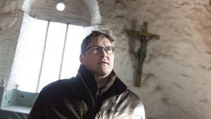 Kirkkoherra Ari Paavilainen Sastamalasta sisällä Tyrvään Pyhän Olavin kirkossa alttarin edessä.