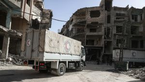 Kaksi Syyrian Punaisen Puolikuun avustuksia kuljettavaa kuorma-autoa ajaa pommitusten raunioittamassa kaupunkimaisemassa