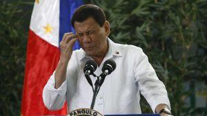 Duterte pitää tiedotustilaisuutta puhujanpöntön takaa. Hänellä on yllään valkoinen kauluspaita. Duterten kasvot ovat rypyssä ja hän koskettaa oikealla kädellään poskipäätään. Taustalla näkyy kasvillisuutta ja Filippiinien lippu.