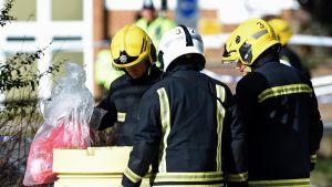 Kolme suoja-asuissa olevaa palomiestä on kumartuneena roska-astian ympärille. Yksi miehistä nostaa astiasta muovipussia.