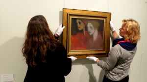 Kaksi naista asettelemassa arvokasta taulua seinälle