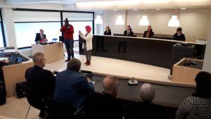 Toimittajat ja kuvaajat ottavat kuvia Ylivieska-Raahen käräjäoikeuden istuntosalissa.