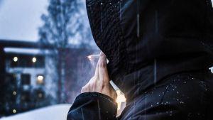Anonyymi nainen seisoo parvekkeella ja polttaa tupakkaa
