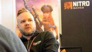 NitoGames pelifirman toimitusjohtaja Jussi Tähtinen istuu työpaikallaan, taustalla yrityksen roll-up
