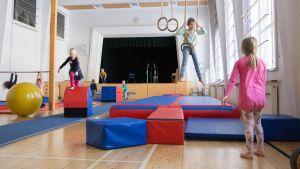 Lapsia leikkimässä liikuntasalissa.