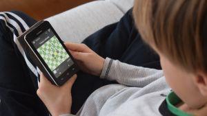 Poika pelaa nettipeliä kännykällä