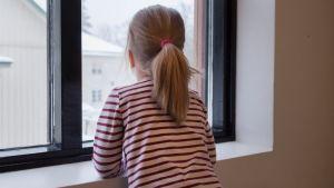 Päiväkodin tyttö katsoo ikkunasta ulos.