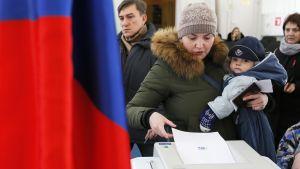 Nainen pudottaa äänestyslippua uurnaan