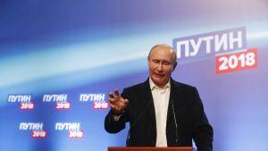 Mies puhujan pöntössä taustalla venäjän kielistä tekstiä.
